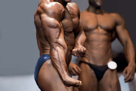tricep: Bodybuilders side tricep pose. Muscular athlete flexing on stage. His first competition. Judges are getting excited. Stock Photo