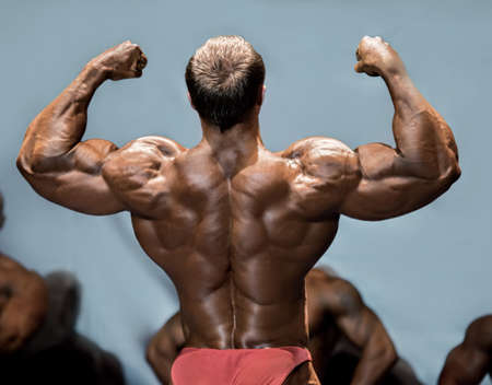 envious: Mans back double biceps pose. Bodybuilder demonstrating arms on stage. Making opponents envious. One more step to victory. Stock Photo
