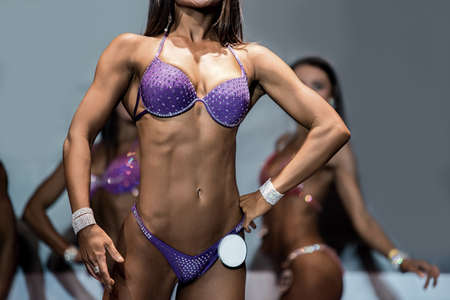 perfect female body: Fitness bikini athletes lean torso. Woman demonstrating fit torso. Beautiful figure and tanned skin. Perfect female body.
