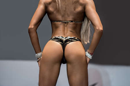 Girls muscular back and butt. Sexy model in dark bikini. Result of correct time investment. Perfect tanned body.