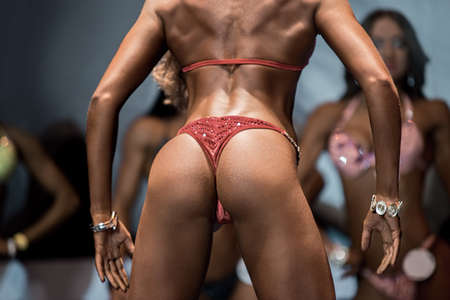 sexy butt: Fitness models sexy butt. Muscular lady shows back muscles. Competiton has just started. Future fitness bikini champion.