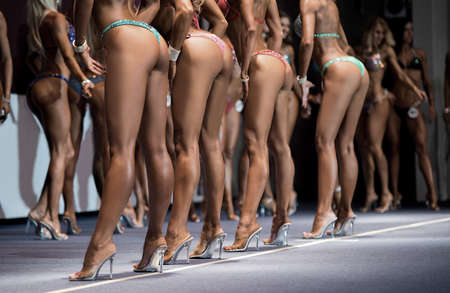 Legs of fitness bikini contestants. Sexy women posing on stage. Youth and beauty. Female competitors demonstrating great form.