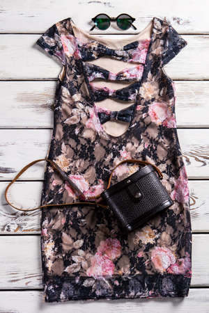 neckline: Deep neckline dress and sunglasses. Stylish evening clothes on shelf. Dark dress with black purse. Become the center of attention. Stock Photo
