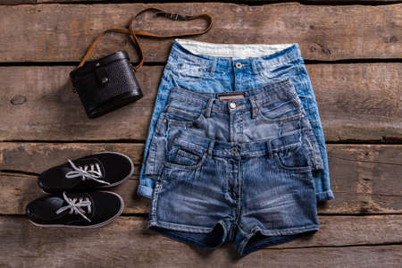 denim shorts: Ladys different denim shorts. Aged shelf with denim garments.Different classic shorts and footwear. Shorts sale at retro boutique.