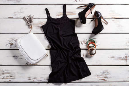 Short dress and black shoes. Glamour outfit on shop showcase. Attractive clothes for young women. Dark female outfit for parties.