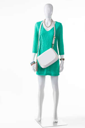 womans clothing: White handbag with turquoise dress. Female mannequin wearing white purse. High-quality leather accessory. Womans clothing and handbag. Stock Photo