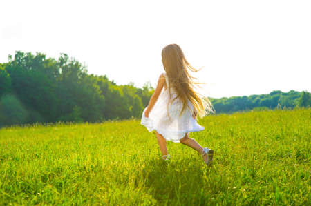 Little girl running on green grass. Beautiful warm summer evening. Standard-Bild