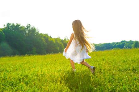 jolie petite fille: Petite fille courir sur l'herbe verte. Belle été chaud du soir. Banque d'images