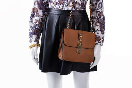 party outfit: Skirt and purse on mannequin. Womans brown leather handbag. Dark skirt with trendy purse. Party outfit for stylish girls. Stock Photo