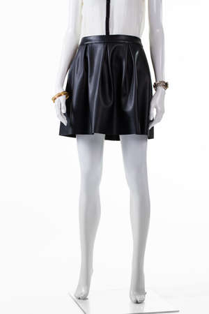 leather skirt: Short leather skirt on mannequin. Dark skirt and wrist accessories. Stylish skirt with small watch. Young ladys outfit for evening.