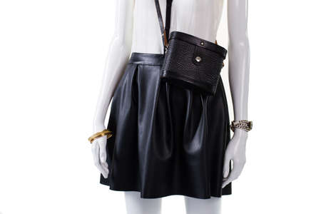 leather skirt: Purse and skirt on mannequin. Retro handbag with leather skirt. Womans fashionable dark skirt. Gold bracelet and black bag. Stock Photo