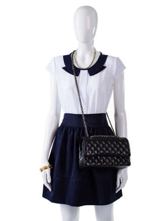 quilted: Mannequin with black quilted purse. Quilted handbag and navy skirt. Womans leather quilted bag. New quilted purse on display.