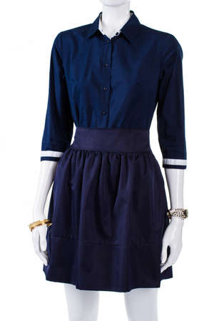 womans clothing: Fitted navy shirt on mannequin. Womans  dark fitted shirt. Plain clothing and wrist accessories. Simple outfit idea for spring.