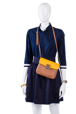 bicolor: Navy shirt with bicolor purse. Mannequin wearing thin bicolor bag. Womans new leather handbag. Dark outfit with light purse. Stock Photo