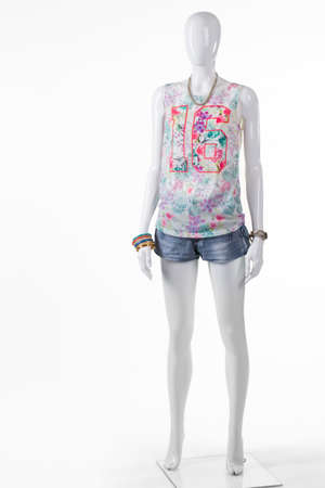 outlet store: Womans short blue denim shorts. Summer denim shorts on mannequin. Colorful top with denim shorts. Summer collection in outlet store. Stock Photo
