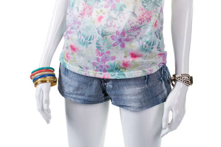 womans clothing: Floral top and wrist accessories. Denim mini shorts on mannequin. Womans small summer shorts. Combination of stylish clothing. Stock Photo