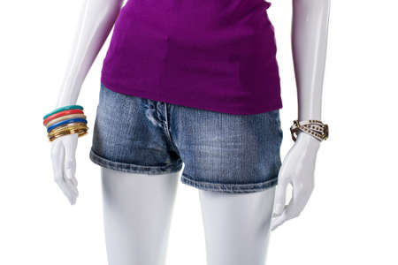 denim: Purple top and denim shorts. Mannequin wearing blue denim shorts. Garment of high-quality denim. Short denim shorts on display. Stock Photo