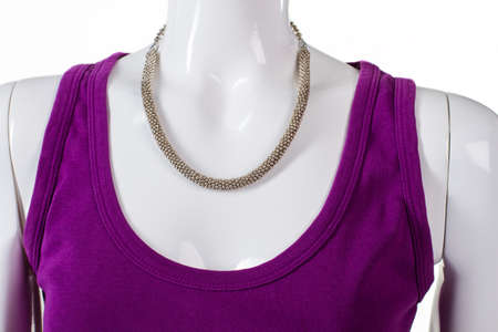 silver jewelry: Purple top with silver necklace. Womans silver jewelry on mannequin. Beautiful silver necklace on showcase. New expensive merchandise. Stock Photo