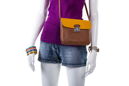 woman's clothing: Purple top with bicolor bag. Purse with strap on mannequin. Womans trendy handbag and shorts. Stylish clothing for modern youth.