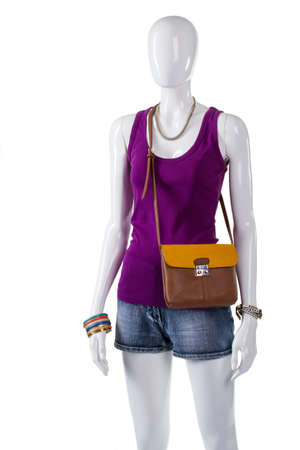 good color: Womans top and bicolor bag. Bicolor purse on white mannequin. Colorful bijouterie with new clothing. Good color combination for clothes.