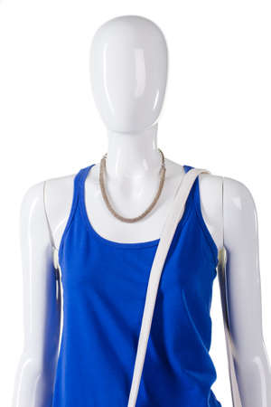 womans clothing: Blue top and white strap. Leather strap over mannequins shoulder. Womans simple high-quality clothing. Spare white strap for bag. Stock Photo