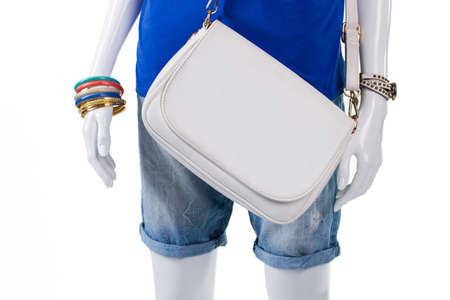 inexpensive: Folded shorts with leather handbag. Simple white bag on mannequin. Colorful bijouterie and plain purse. Inexpensive leather handbag in stock.