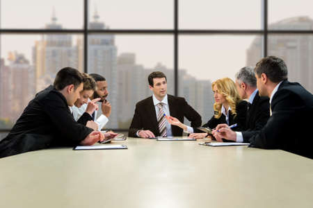 collectives: Businesspeople talking at the table. Collectives lively discussion at daytime. Every day should bring results. Step towards the common goal. Stock Photo