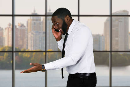 phonecall: Friendly black guy with cellphone. Managers phonecall on city background. Businessman establishing contacts. Manners mean a lot.