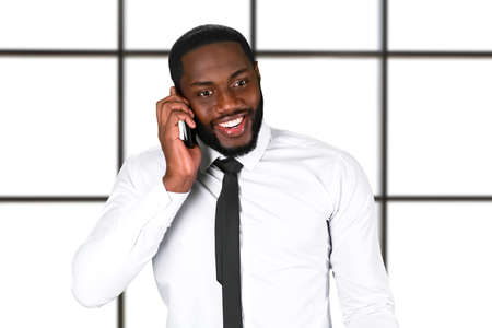 contacting: Happy black man with phone. Friendly executive on white background. Contacting a new partner. Make friends and shape future.