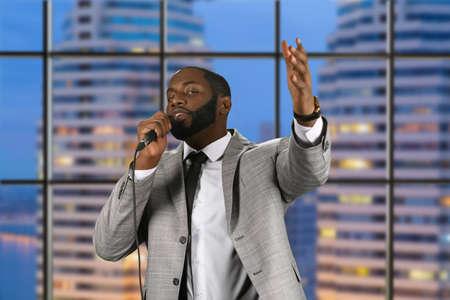 preacher: Black preacher speaking into microphone. Bearded preacher on evening background. Evening prayer in city church. Strengthen your faith.