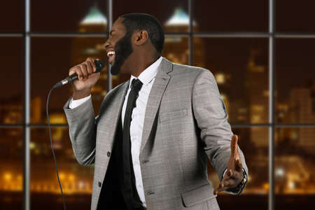 vocalist: Expressive black singer with microphone. Vocalist on night city background. Blues performance in capital city. His voice is unbelievable.
