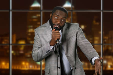 showman: Expressive black man with microphone. Stand-up comedian on night background. Comedy show on local television. Old funny story.