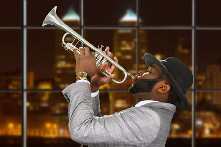 megalopolis: Darkskinned trumpeter in fedora hat. Trumpeter playing in night megalopolis. Music and passion are one. Young talent from capital city. Stock Photo