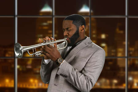 composers: Black man plays the trumpet. Jazz trumpeter on night background. Composers outstanding trumpet solo. Musician and instrument are one. Stock Photo