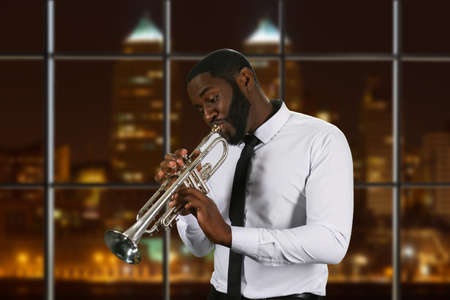 night shirt: Darkskinned trumpeter in white shirt. Trumpeter on night city background. Enthusiastic and talented man. Music flows through him.