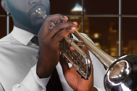 skillful: Afro mans hand on trumpet. Young trumpeter in night megalopolis. Composers inspiring music. Skillful blues performer. Stock Photo