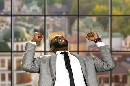 the victorious: Afro businessman expressing joy. Victorious man on urban background. Sweet moment of joy. Happy and fearless.