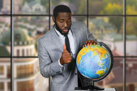 endorsement: Darkskinned man with globe. Businessman showing thumb up. The teachers endorsement. Globe on urban background.