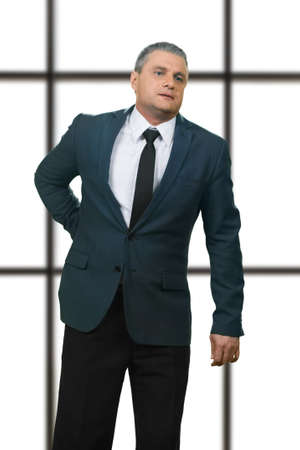 diseased: Adult businessman having back pain. Diseased manager on white background. Serious kidney injury. Problem that needs treatment. Stock Photo