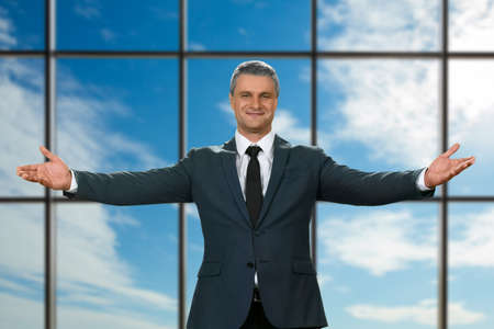 polite: Adult businessmans welcoming gesture. Polite executive on sky background. Best chief ever. Its all for you.