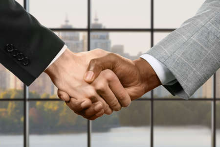 meet and greet: Businesspeople shake hands. Business handshake on daytime background. Our negotiations were successful. In the name of progress.