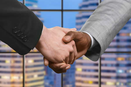 formally: Formally dressed men shaking hands. Evening handshake of executives. Strong friendship of nations. Agreement between companies.