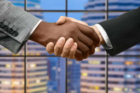 an ally: Afro and caucasian businessmens handshake. Handshake in front of skyscraper. What goes around comes around. Happy to meet new ally.