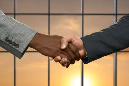deception: Adult businessmen shaking hands. Handshake on sunny sky background. Partnership begins from simple things. Honesty or deception. Stock Photo