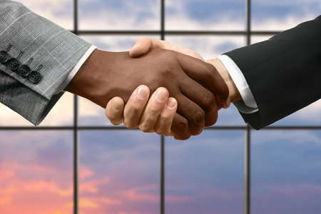 formally: Formally dressed men shake hands. Business handshake on sunset background. Agreement of serious people. Nations become friends. Stock Photo