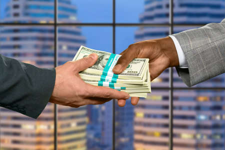 pack of dollars: Businessmans hand taking big money. Repaying debt in the city. He gained a significant percent. Good month for a salesman. Stock Photo