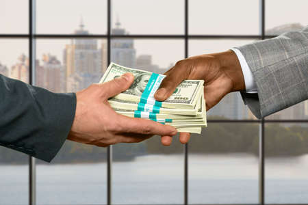 inheritance: Male hand taking big money. Money transfer on city background. Strong leaders inheritance. Purchasing real estate on credit. Stock Photo