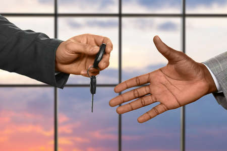 drive safely: Mans hand passing car key. Car key on sunrise background. Always drive safely. Luxury is not for everyone.