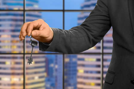 special agent: Hand of businessman holding key. Estate agent on evening background. The new apartment is yours. Special gift for company employee.