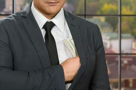 venality: Businessman hiding dollars into jacket. Man with cash at daytime. Mind every step. Profitable deal gone well.